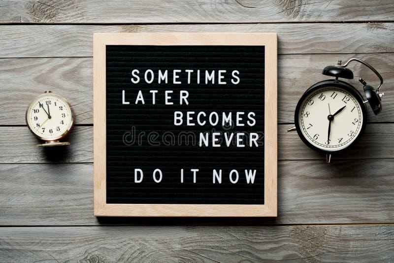 Inspirationsmotivierendes Zitat Manchmal wird später nie Jetzt Wörter auf einem Briefbrett auf Holzboden in der Nähe stockbild