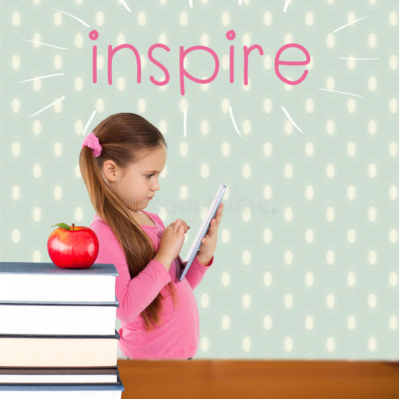Inspire against red apple on pile of books. The word inspire and cute girl using tablet against red apple on pile of books stock photos