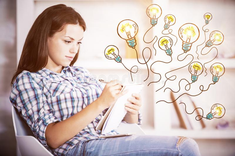 Inspire concept. Side view of attractive young woman drawing or writing in notepad with abstract drawn light bulb balloons while sitting in modern office royalty free stock photos