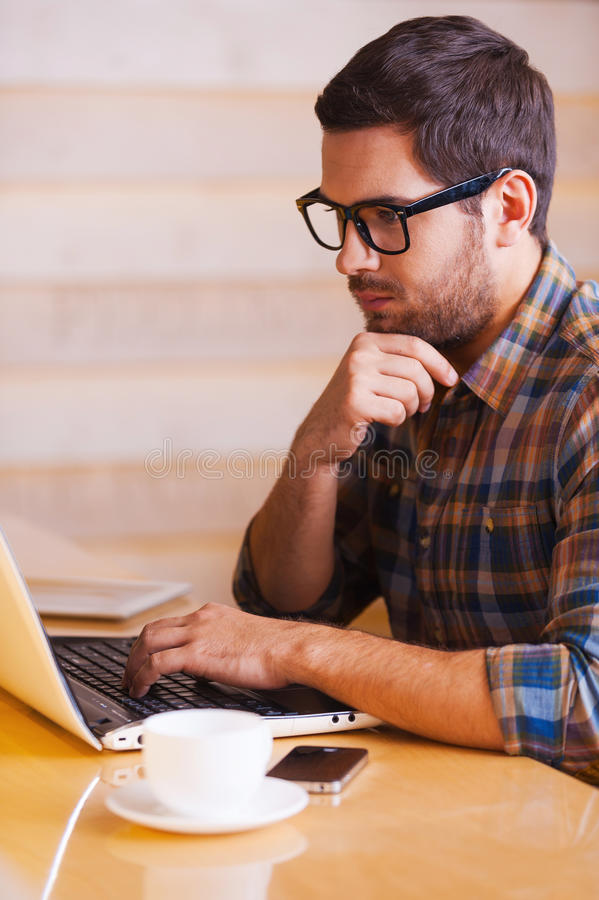 Inspire with cup of fresh coffee. Confident young man working on laptop while sitting in coffee shop royalty free stock images