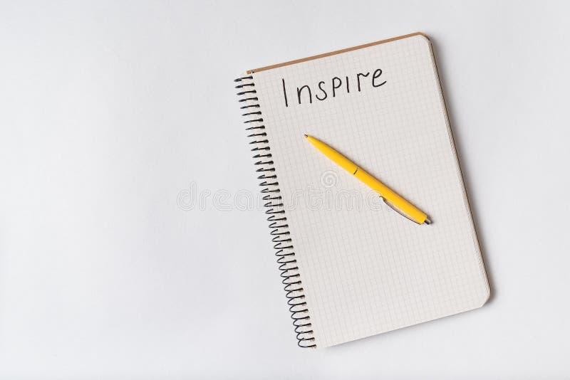 INSPIRE-Handschrift Obere Ansicht von Notepad und Stift auf weißem Hintergrund lizenzfreies stockbild