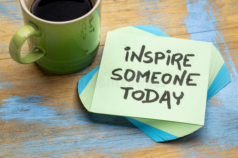 Inspire someone today note with coffee. Inspire someone today - advice or reminder on a sticky note with a cup of coffee stock image