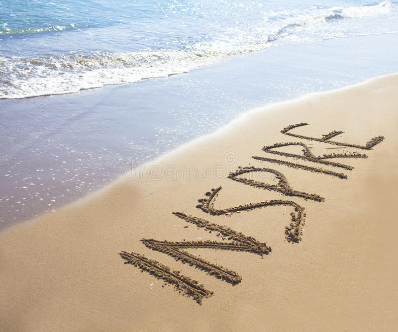 Inspire. Written on sand on a beach stock image
