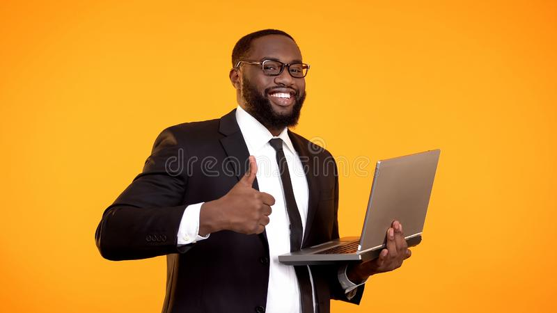 Inspired afro-american office employee holding laptop and showing thumbs-up royalty free stock photos