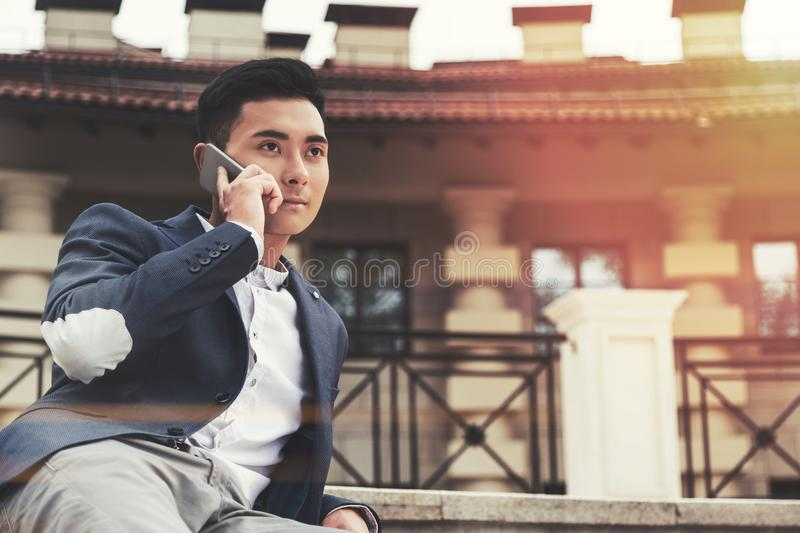 Inspired Asian businessman on phone in a city royalty free stock photography