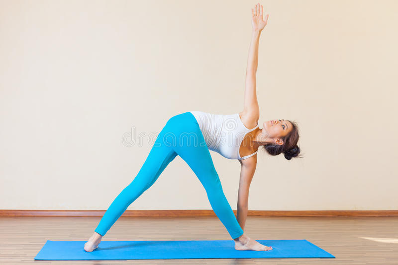 Inspired asian woman doing exercise of yoga indoor. At class of yoga. Concept of a healthy lifestyle, sport and the right attitude to life royalty free stock photography