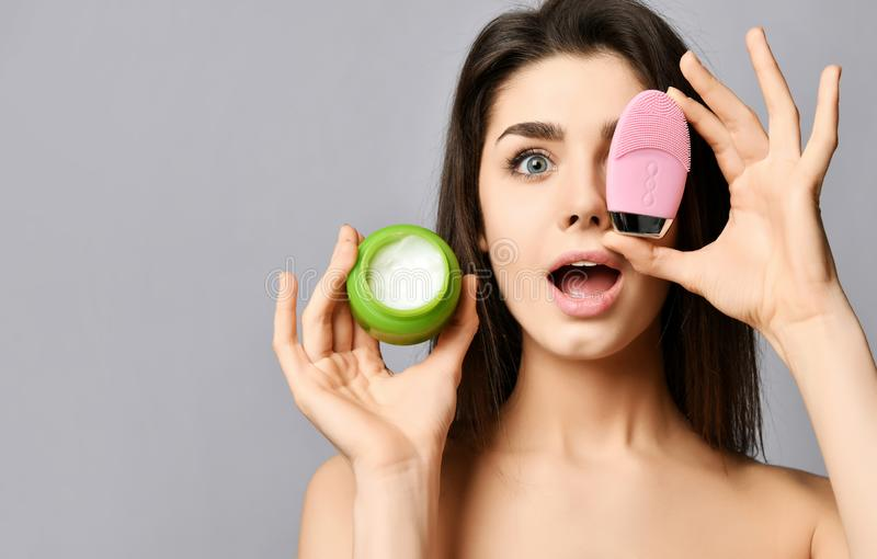 Inspired beautiful woman covers her eye with pink face brush silicone cleansing device for skin and shows a jar of face cream. Background. Text space stock image