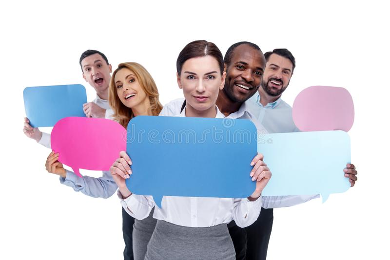 Inspired co-workers holding tables and smiling stock images