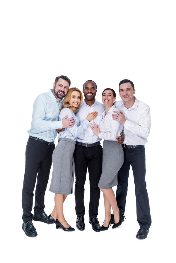 Inspired colleagues standing together and hugging stock photography