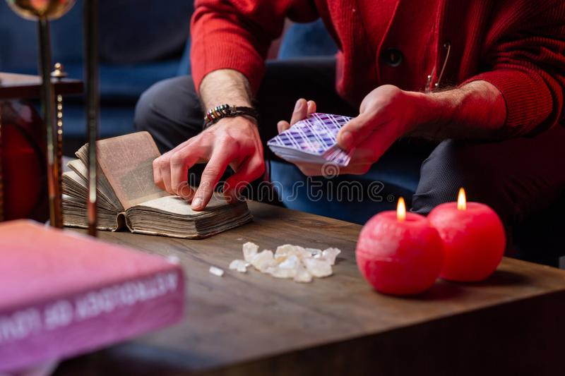 Inspired fortune-teller using old little magic book while reading cards stock images