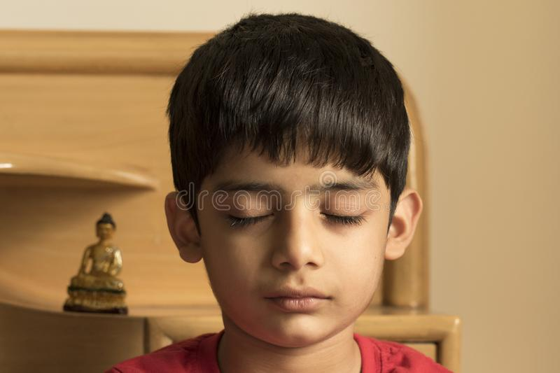When meditation is done by a small boy. Inspired by Gautama Buddha, a small boy is trying to meditate stock image