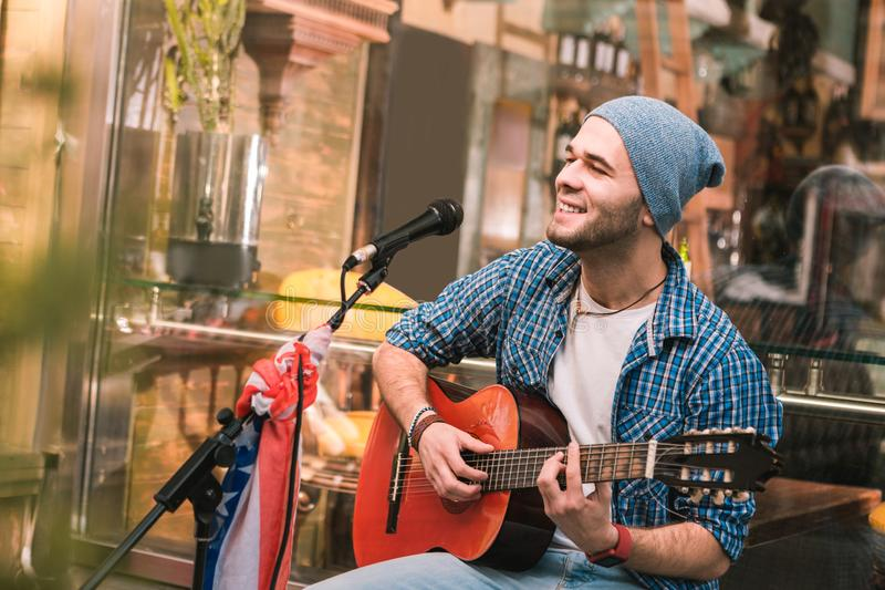 Inspired male guitarist performing song in bar royalty free stock image