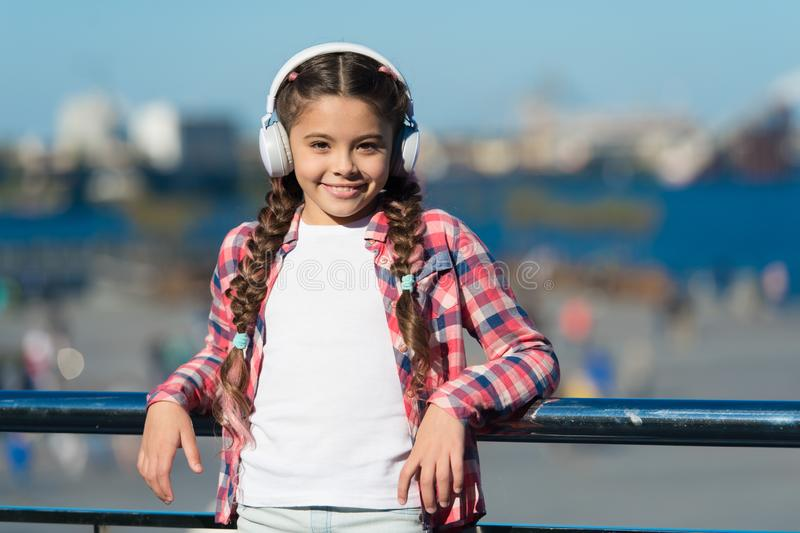 Inspired by music. Little kid listening to music. Cute kid with wireless headset. Small kid wearing stereo headphones royalty free stock images