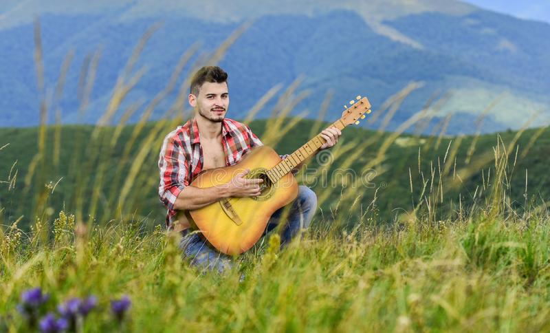 Inspired musician play rock ballad. Compose melody. Inspiring environment. Acoustic music. Man with guitar on top of. Mountain. Summer music festival outdoors stock photography