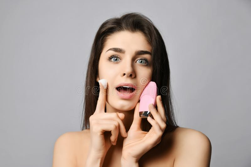 Inspired by pleasure of softens of her skin woman with pink face exfoliator brush silicone cleansing device for skin. Inspired by pleasure of softens of her royalty free stock photo