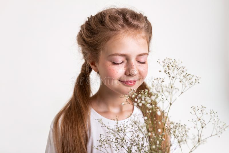 Inspired tranquil little girl smelling scent of flowers royalty free stock photography