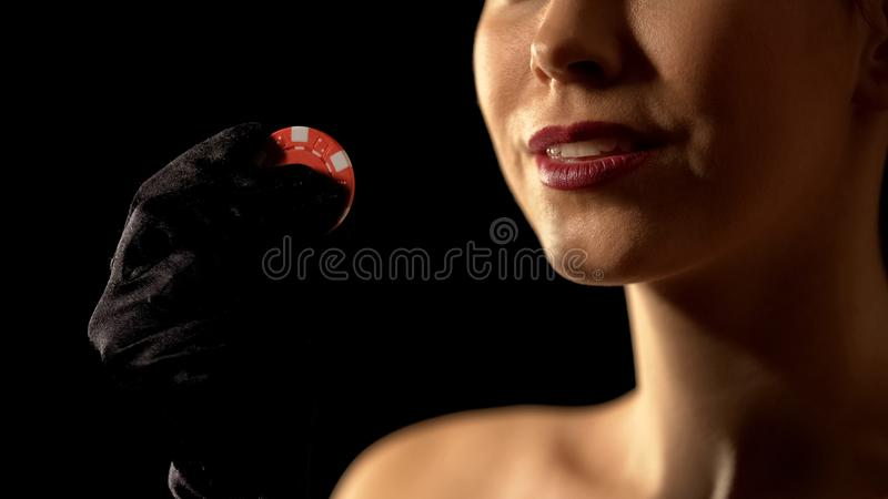 Inspired woman showing gambling chip to camera, chance for winning, casino. Stock photo stock images