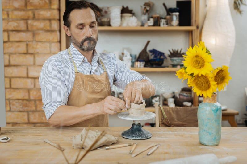 Inspirerad ceramist som gör hans berömda vaser för blommor royaltyfri bild
