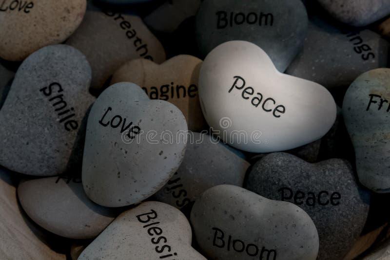 Inspirerande hjärta formade stenar i korg arkivfoton
