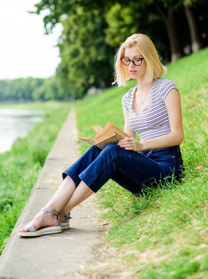 Inspirerat av den nya författaren studentflicka med den utomhus- boken kvinnan parkerar in läseboken intressant ber?ttelse Koppla royaltyfria foton