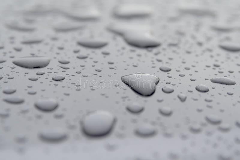 Inspirierend Herz formte Regenwassertropfen auf grauer Oberfläche lizenzfreies stockfoto
