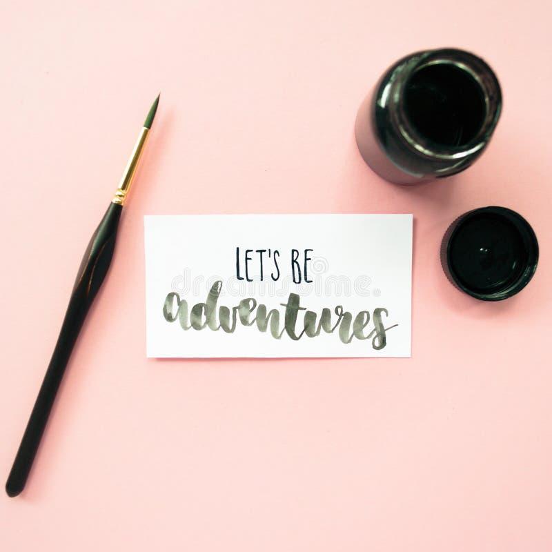 Inspirierend Zitat ließ ` s Abenteuer, Tinte, Pinsel sein auf einem blassen - rosa Pastellhintergrund Künstlerarbeitsplatz stockfotografie
