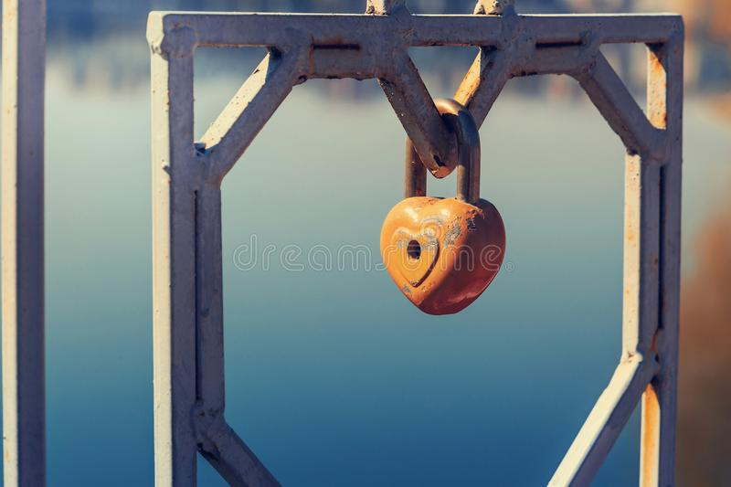 Inspiring spring morning. Old padlock - the heart. attached to the fence by the lake. In a city park. concept of love.toned stock image