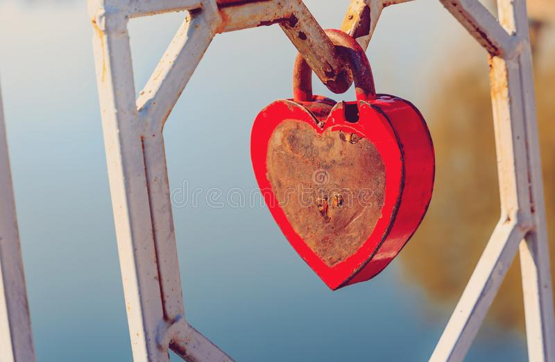 Inspiring spring morning. Old padlock - the heart. attached to the fence by the lake. In a city park. concept of love.toned stock photography