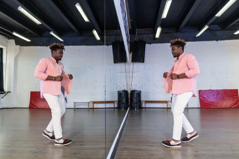 Inspirowany elastyczny mężczyzna w różowej koszulowej pozycji przed pełnym długości lustrem zdjęcia stock