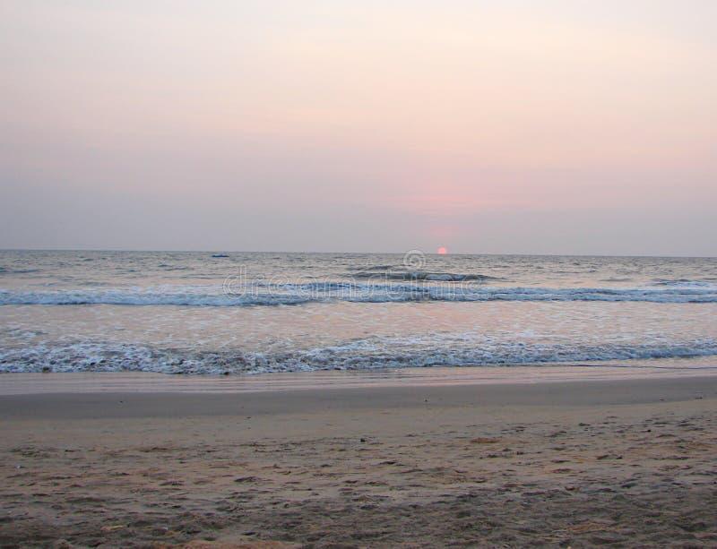 Inställning av den röda solen på horisonten över havet på den Payyambalam stranden, Kannur, Kerala, Indien royaltyfria bilder