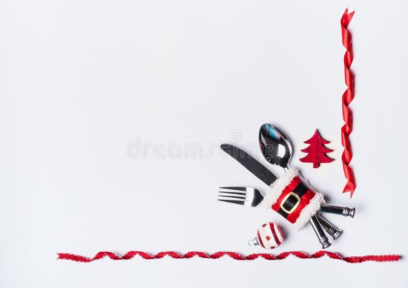 Inställning för julmatställetabell med bestick som dekoreras med jultomten bälte, julgran och band på vit bakgrund, bästa sikt royaltyfria foton