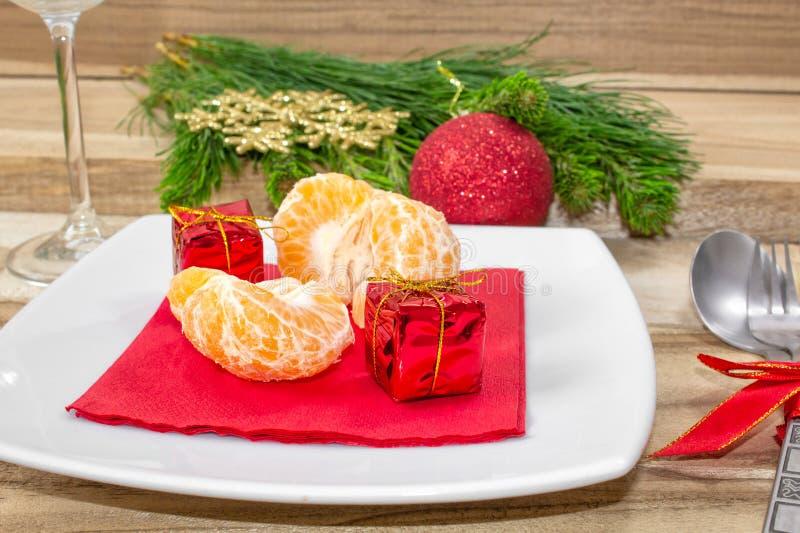 Inställning för jultabellställe festlig bakgrund Filialer av gran, bollar, bestick och tangerin royaltyfria bilder
