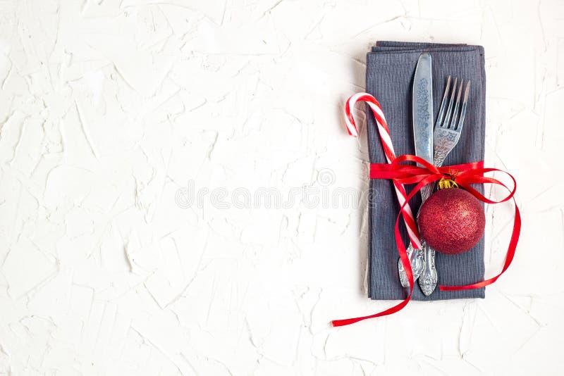 Inställning för jultabellställe med kniven, gaffeln, den röda bollen, godisrottingen och bandet över den vita tabellen med copysp arkivfoto