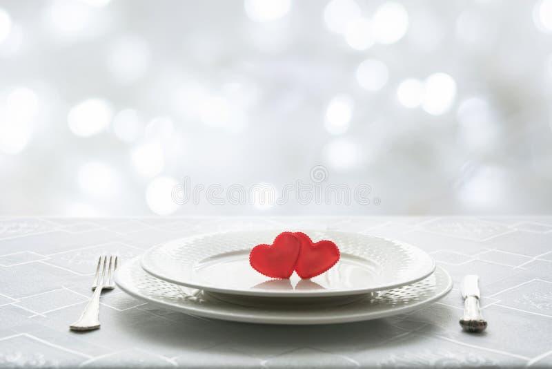 Inställning för ställe för valentindagtabell med två hjärtor Utrymme för text Inbjudan för ett datum royaltyfri foto