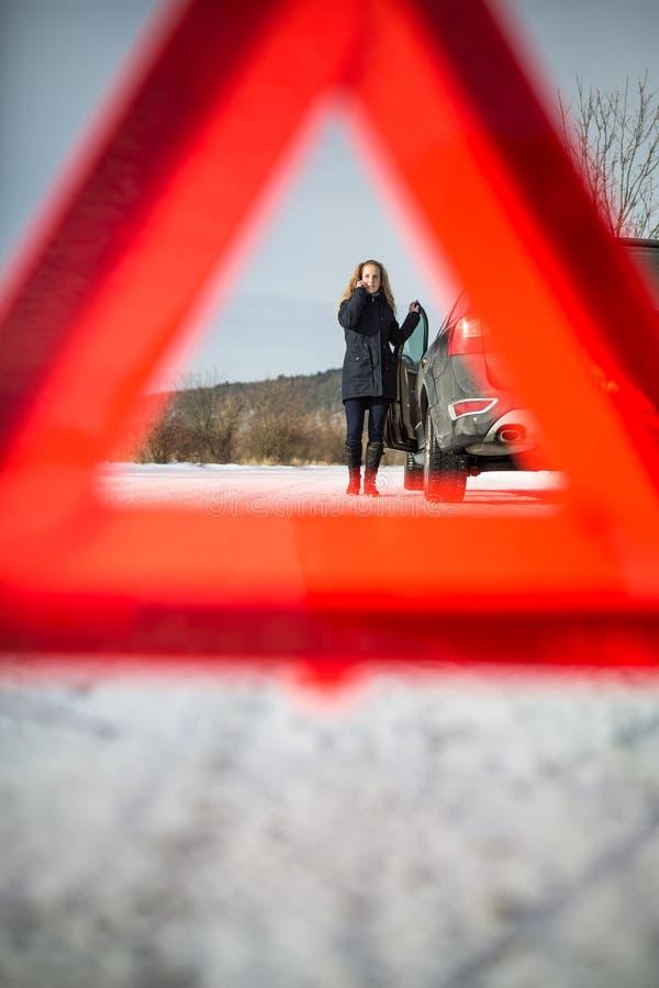 Inställning för ung kvinna - upp en varningstriangel och att kalla för assistence arkivbild