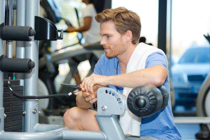 Inställning för ung man - upp konditionmaskinen på idrottshallklubban fotografering för bildbyråer