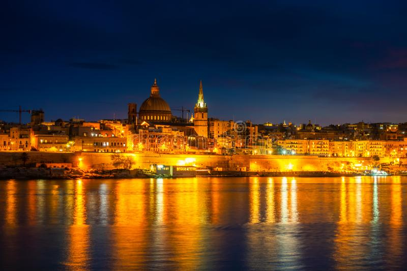 Inställning framför nattscenen i Basilica Vårt Lady Mount Carmel i Valletta från Sliema, Malta arkivfoto