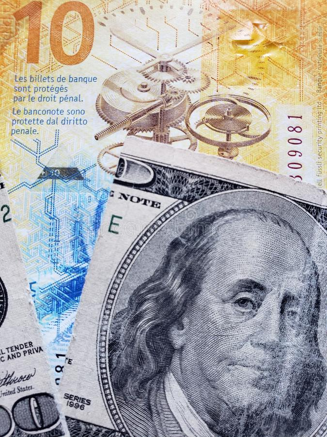 inställning till den schweiziska sedeln av tio franc och den brutna amerikanska sedeln av 100 dollar, bakgrund och textur arkivbild