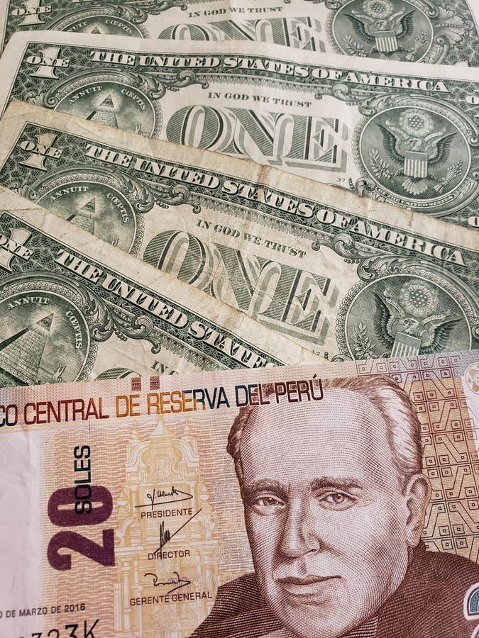 inställningen till den peruanska sedeln av tjugo sular och amerikanska en dollar räkningar arkivbild