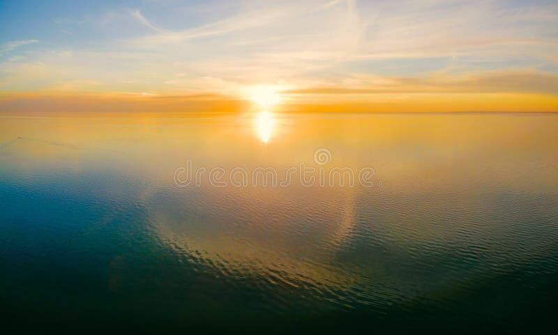 Inställningssol över lugna vatten med molnreflexioner royaltyfria bilder