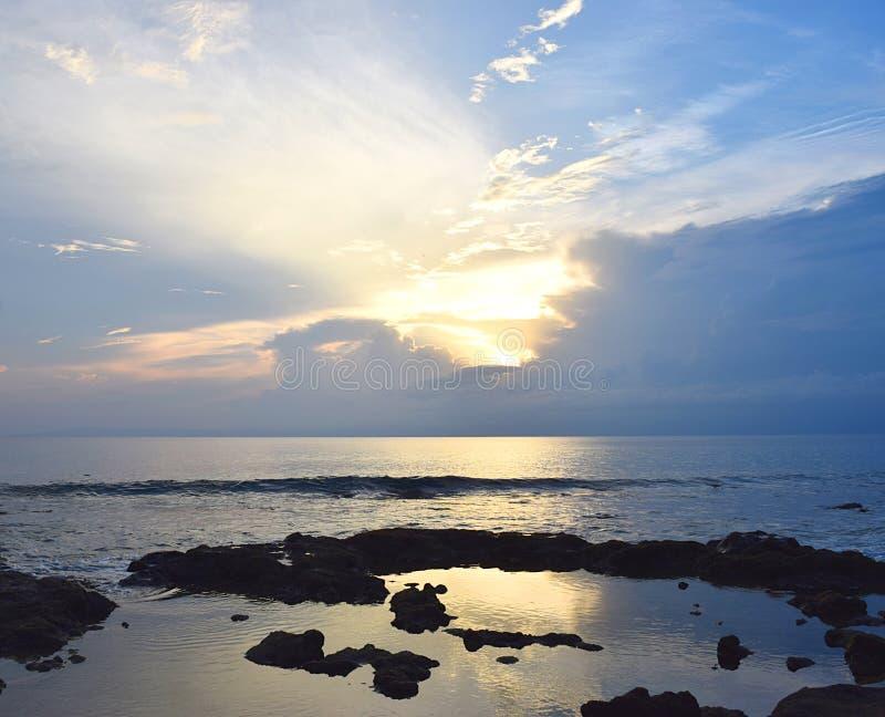Inställningssol bland moln över havet på horisonten med ljusa guld- solstrålar i himmel - Neil Island, Andaman Nicobar, Indien royaltyfria bilder