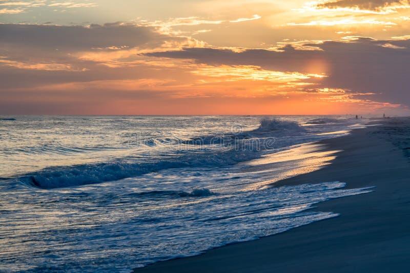 Inställningssol som tänder inkommande vågor och stranden royaltyfri foto