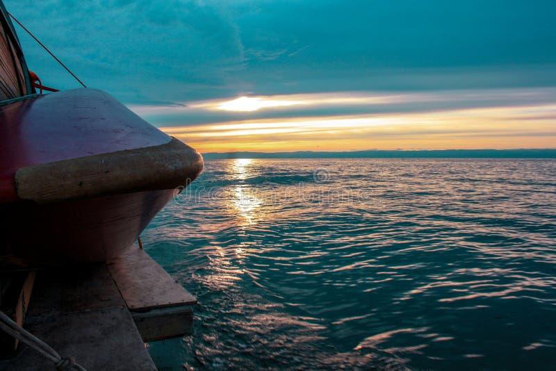 Inställningssolen exponerar det blåa vattnet av sjön royaltyfri foto