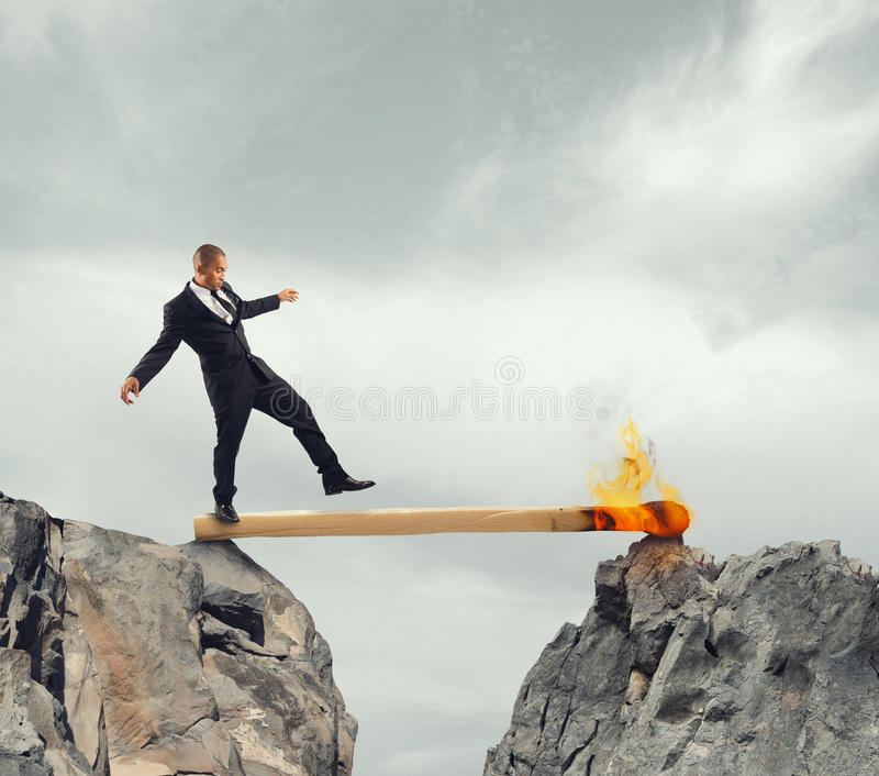 Instability and Fear of obstacles to overcome. Businessman walk over a match lit between two mountains stock image