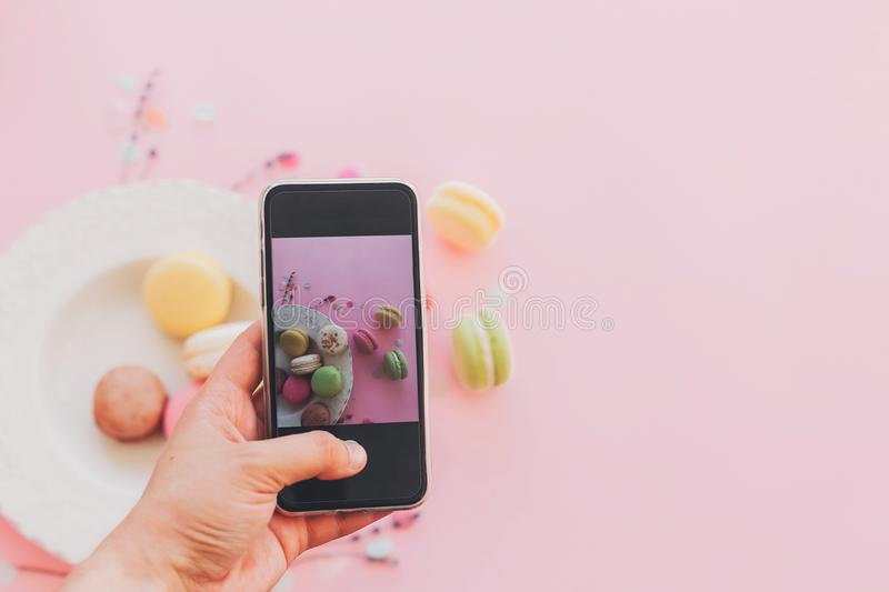 Instagram blogging concept, flat lay. food photography. hand holding phone and taking photo of stylish colorful macaroons in. Vintage plate on trendy pink paper royalty free stock photo