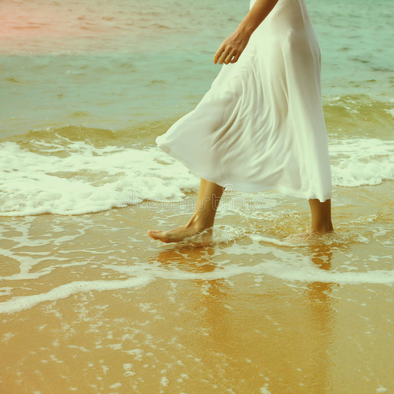 Instagram colorized vintage female legs. Instagram colorized vintage body part outdoor portrait of young woman's legs in white cotton skirt walking along coastal royalty free stock photos