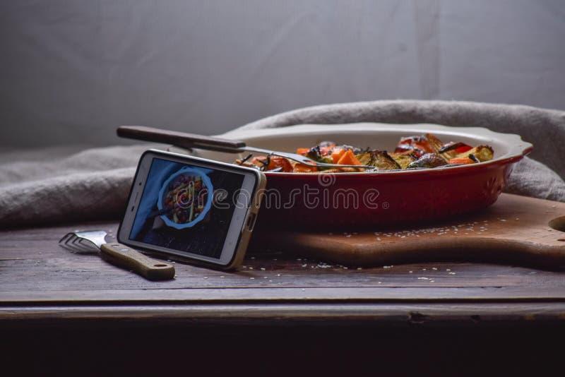 Instagram fotografii blogging warsztatowy pojęcie dzwoni blisko eleganckiego talerza z piec na grillu vegatables na drewnianym ni obraz royalty free