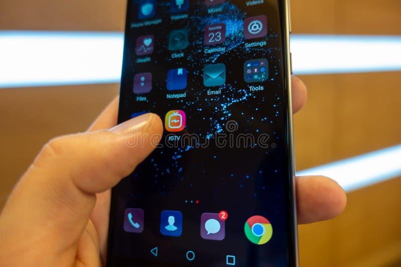 Instagram IGTV Человек отжимает телефон IGTV кнопки Крупный план значка IGTV стоковые фотографии rf