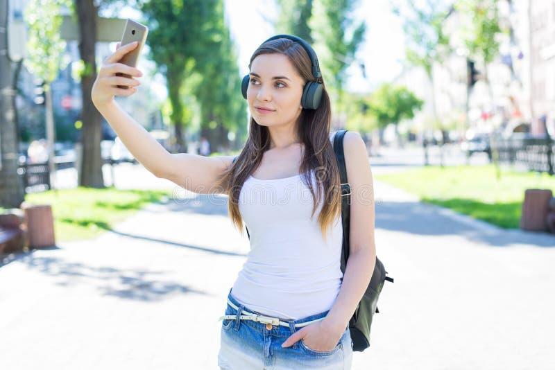 Instagram influencer小配件设备学生牛仔布衣裳概念 相当可爱的华美的好确信的夫人照片画象  免版税库存图片
