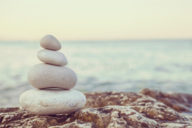 Instagram Pile of Stones on Tranquil Beach at Sunset royalty free stock images